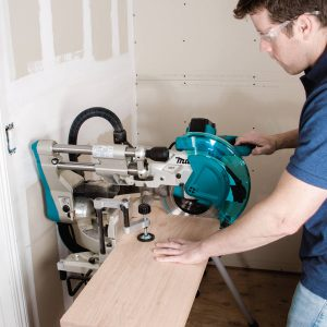 Makita LS1019L crosscutting a wide board backed against a wall