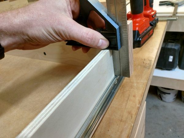 Using a combination square to line up the drawer slide on the drawer