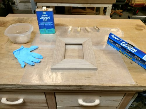 Picture frame laid out with material used to apply an oil finish