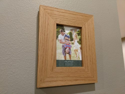 Completed picture frame I built hanging on the wall with a photo
