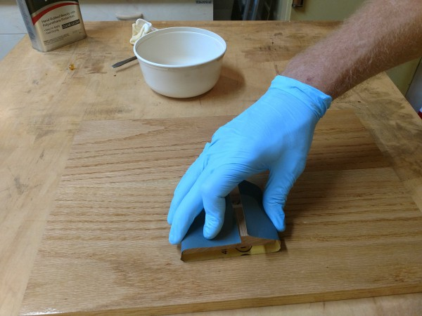 Wipe on poly being applied with block and sandpaper