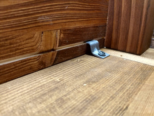 Attaching table top to apron using metal fasteners - closeup