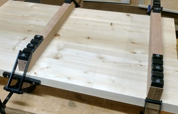 table top being clamped and glued using panel clamps
