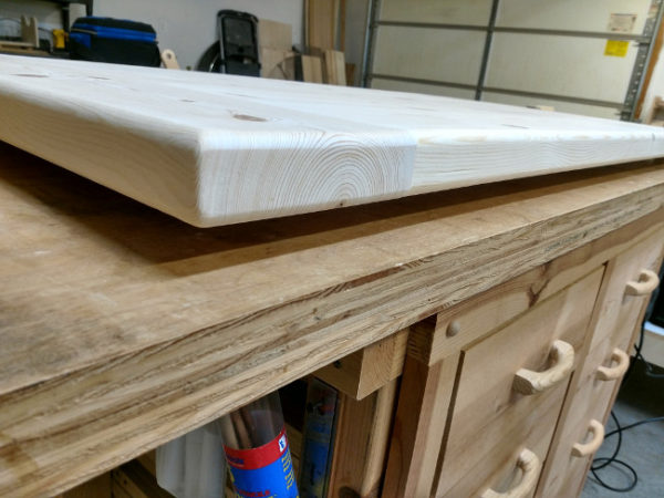 Piece getting stained is elevated from work bench with wood blocks