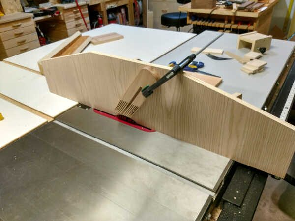 Feather board clamped to a sac fence