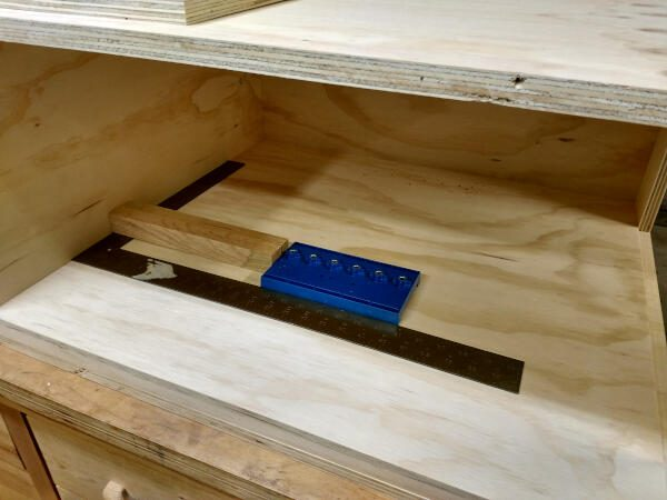 using block of wood to position shelf pin jig