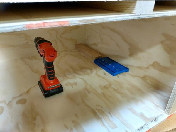 shelf pin jig positioned with block of wood