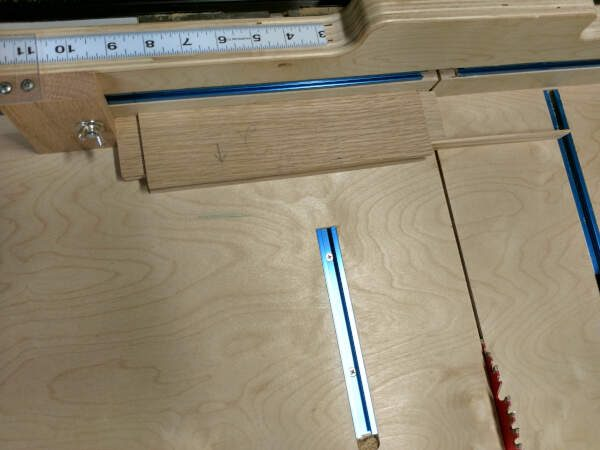 Cabinet doors frame rail lined up for cut with stop block on the table saw sled