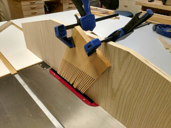 feather board clamped to a table saw sacrificial fence